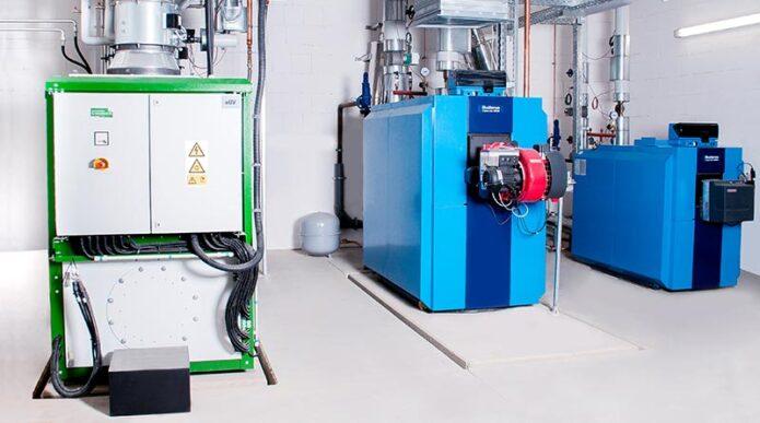 Eine von vielen Möglichkeiten: In dieser Heizzentrale eines kalten Nahwärmenetzes wird mithilfe von Kraft-Wärme-Kopplung (KWK) Strom und Wärme produziert. Das Erd/Biogas-Blockheizkraftwerk (links) liefert dabei die notwendige, elektrische Antriebsenergie für die Wärmepumpen, respektive Übergabestationen. Bildquelle: ratiotherm GmbH & Co. KG, Dollnstein